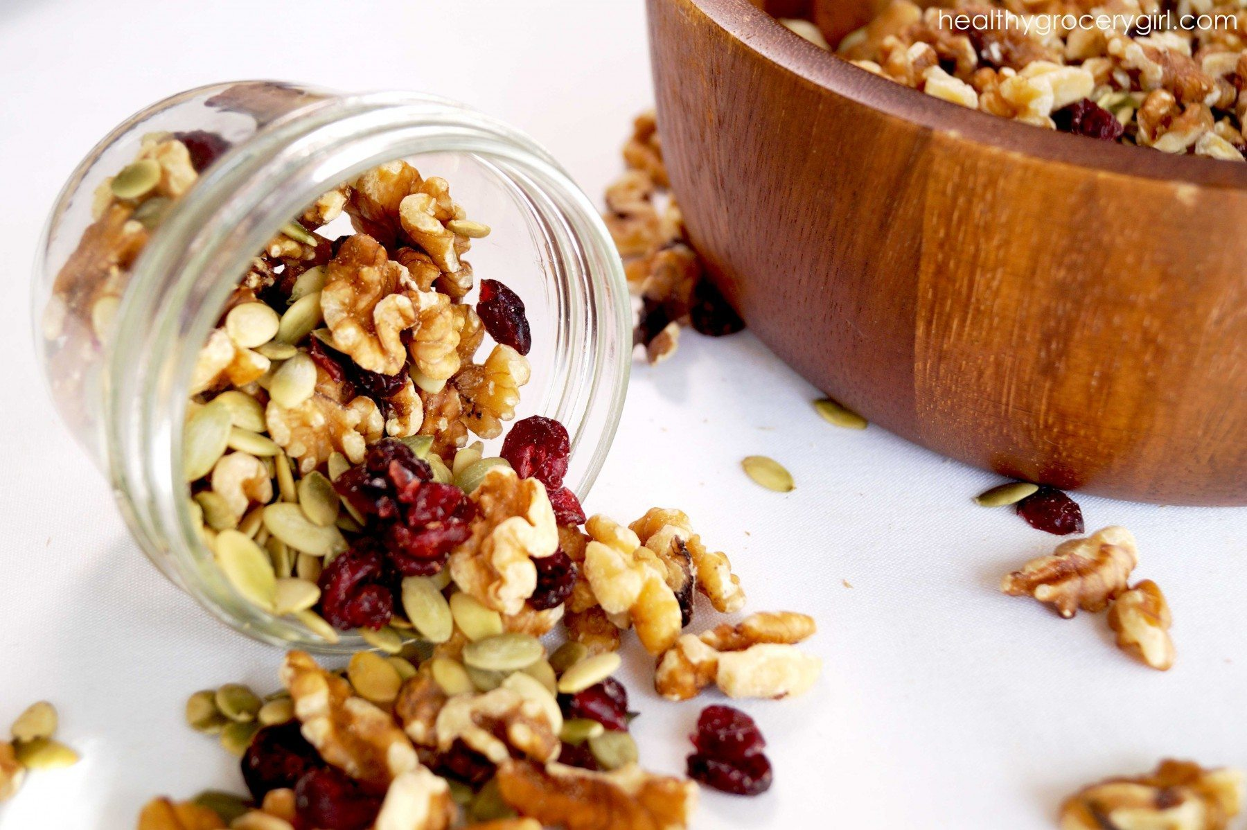 Fall trail mix spilling out featuring walnuts and dried berries